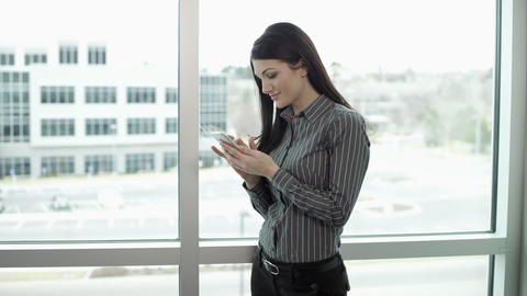 Panning view of woman standing by windows texting Footage