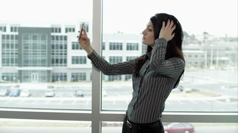 Woman taking photos with smartphone of herself Footage