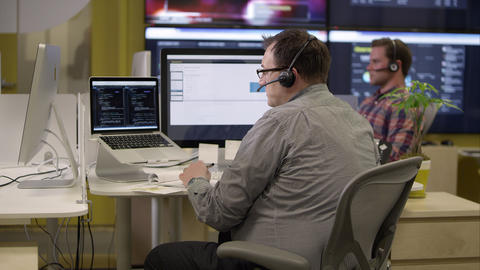 View of 2 people with headsets on in front of computers Footage