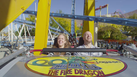 Slow motion shot of a happy couple riding on a rollercoaster Footage