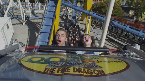 Slow motion shot of front seat of rollercoaster. Couple is screaming Footage