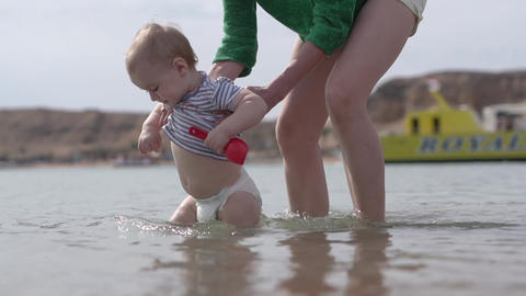 Small kid walk in the water with mother that protect him in slow motion Footage