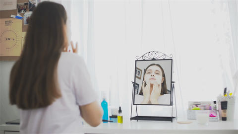 Woman applying cosmetic mask in the room in front of the mirror Footage