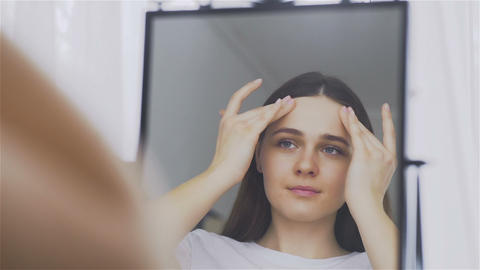 The portrait of young woman with perfect skin applying a day-night cream on her Live Action