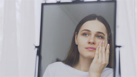 Portrait of a young woman with cream or cosmetic mask on her face Footage