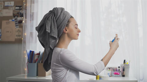 Young woman in towel using hair spray Footage