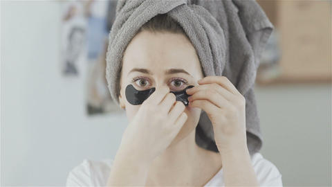 Woman with towel on head imposes under eyes patches of a refreshing Collagen Live Action