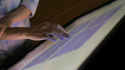 Woman using interactive touchscreen display at modern museum Live Action