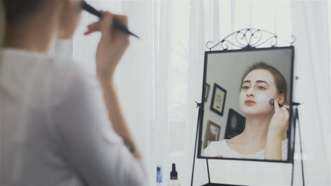 Woman applying cosmetic mask in the room in front of the mirror Live Action