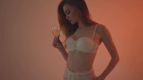 Girl in white underwear drinks white wine . Slow motion 60fps Footage