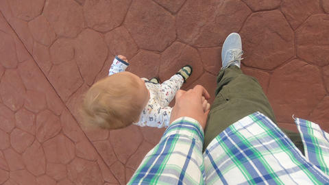 Dad and baby go holding hands on a stone road, view from above in slow motion Footage