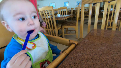Little baby licks the spoon in the highchair in slow motion Live Action