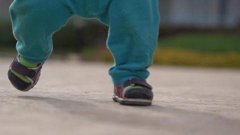 Legs of the little kid in slow motion walks on the street Footage