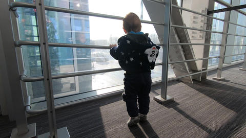 A small child stands near the window and watches the cars, slow motion Archivo