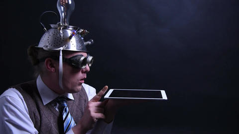 Nerd with aluminum hat looks at his tablet Live Action