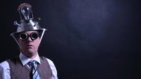 Nerd with aluminum hat looks into the camera Live Action