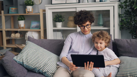 Adorable boy watching cartoons on tablet with his caring mother holding gadget Live Action
