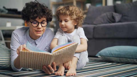 Caring mom reading book to small curious boy relaxing on floor in light house Footage