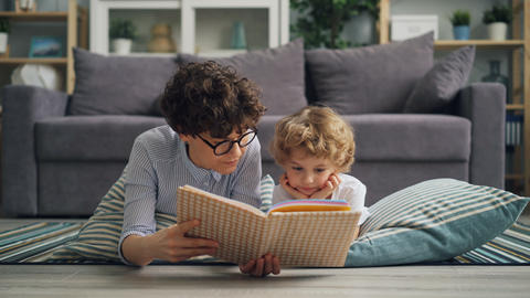 Cute boy listening to fairy-tale while his mother reading book lying on floor Footage