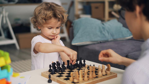 Smart boy playing chess with mother moving pieces expressing positive emotion Live Action