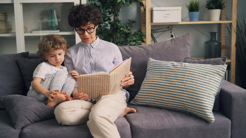Cheerful woman reading funny story to little boy laughing having fun at home Footage
