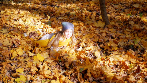 Little cute girl jumping into leaves at park in autumn and trees Footage