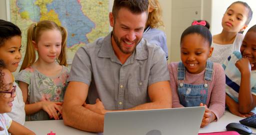 Caucasian male teacher teaching school kids on laptop in classroom at school 4k Live Action