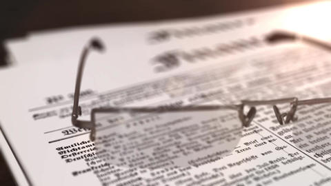glasses with newspaper with the headline Finance on a table Animation