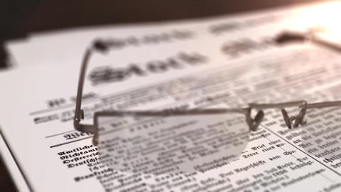 glasses with newspaper with the headline Stock Market on a table Animation