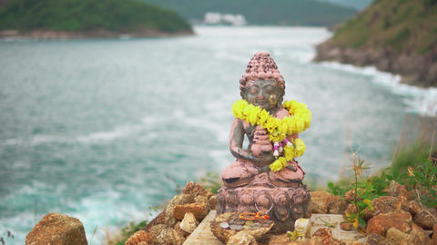 Statue of a deity with a garland of yellow flowers, close-up. Tranquility and Live Action