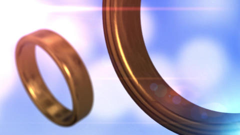 2 golden wedding rings that merge together with beautiful blue bokeh background Animation