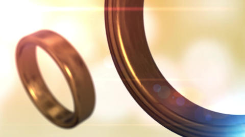 2 golden wedding rings that merge together with beautiful yellow bokeh Animation