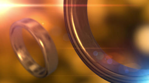 2 golden wedding rings that merge together with beautiful golden bokeh Animation