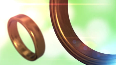 2 golden wedding rings that merge together with beautiful green bokeh background Animation
