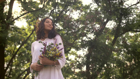 Natural beauty girl with bouquet of flowers outdoor in freedom enjoyment concept Live Action