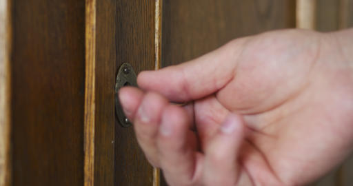 Person by hand turns old key in the keyhole of antique wooden cabinet Footage