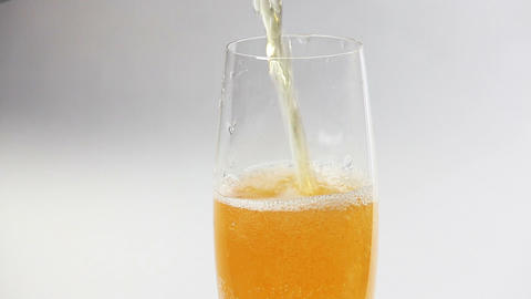 Cider flowing into the glass with bubbles isolated on white Stock Video Footage