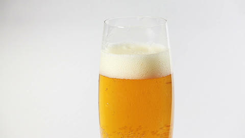 Cider flowing into the glass with bubbles isolated on white Footage