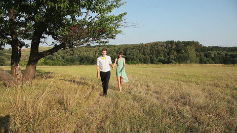 Young couple walking on the yellow grass Stock Video Footage
