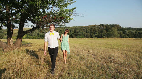 Young couple walking on the yellow grass Footage