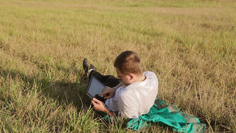 Young man browsing in Internet with tablet lying on the... Stock Video Footage