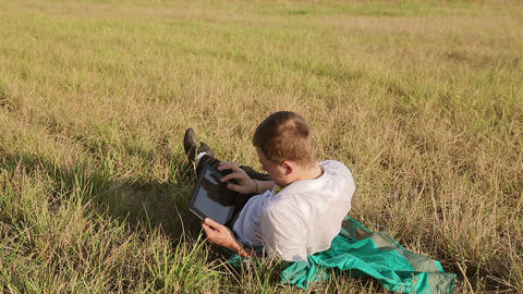 Young man browsing in Internet with tablet lying on the grass Footage