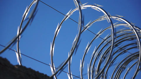 Razor Wire Close Up Pan Against a Blue Sky Stock Video Footage
