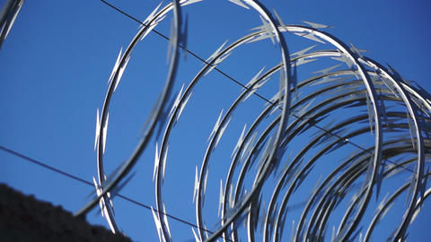 Razor Wire Close Up Pan Against A Blue Sky stock footage