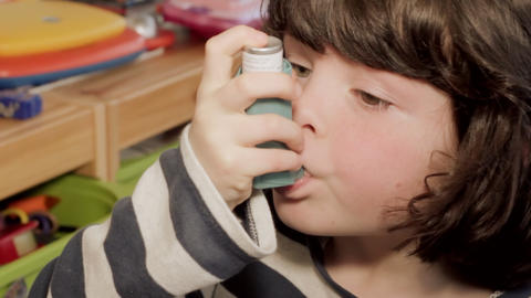 Small girl using asthma inhaler Footage