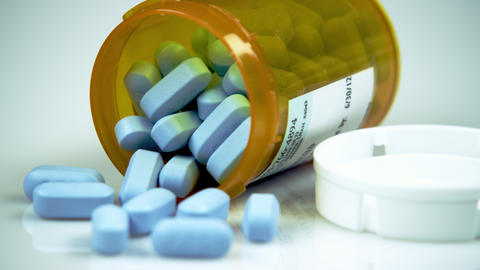 Blue pills in an open prescription bottle Live Action
