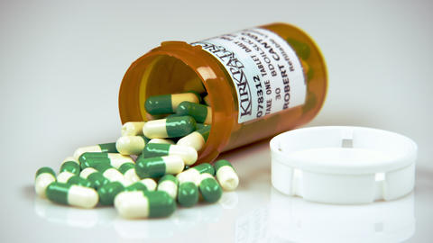 Prescription bottle containing green and white pills Footage