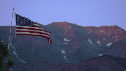 United States flag waving in front of a mountain Footage