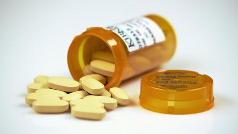 Yellow pills in an open prescription bottle Footage