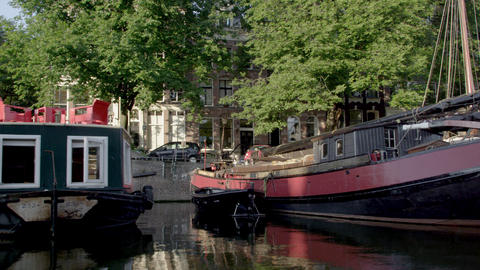 Tracking shot of buildings and houseboats along the Amsterdam Canal in Netherlan Footage